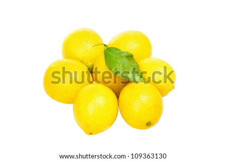 Some lemons with one green leaf isolated on white background