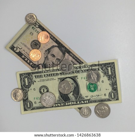 some money on a table, both bills and coins.  in particular, one dollar bill, five dollar bill, pennies, nickels, dimes, and quarters.