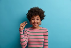 Some more, please. Cheerful smiling African American woman gestures small size with fingers, asks for little bit time, measures too small object, shows something minimum dressed casually stands indoor