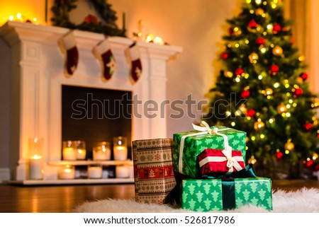 Some nice christmas presents in a living room filled up with winter holidays magic atmosphere. Decorated present with ribbon by the warm cozy fireside. Christmas and Winter Holidays Background.
