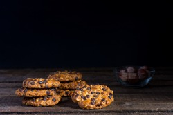 Some oats cookies with hazelnuts and chocolate chips on an old wooden table, a glass bowl with hazelnuts and dark background