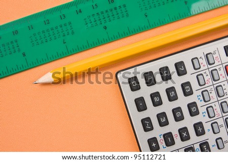 some of school supplies. calculator,pencil and ruler on orange background