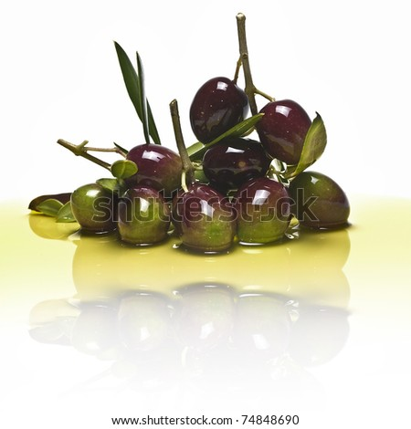Some olive branches with premium olives and leaves over a white background and reflected on water.