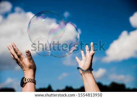 Some one trying to catch soap bubbles. Hands trying to catch  floating soap bubbles Foto stock ©