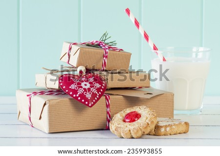 Some paper parcels wrapped (with paper kraft) tied (with red & white baker\'s twine) with tags, two shortbreads and a milk glass. A red heart.  A white table with a turquoise wainscot. Vintage Style.