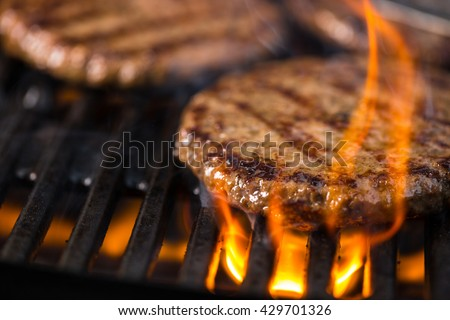 Some patties of ground meat with a flame in the front on cooking grate.