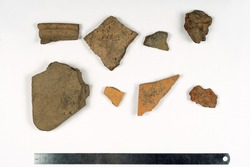 Some peices of clay aged-damaged ceramic artefacts found during the archaeological excavations settled on the sheet of paper with metal ruler. Copy space, close up.