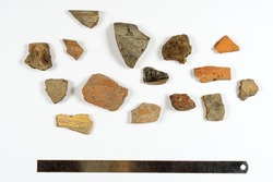 Some peices of clay aged- damaged ceramic artefacts found during the archaeological excavations settled on the sheet of paper with metal ruler. Copy space, close up.