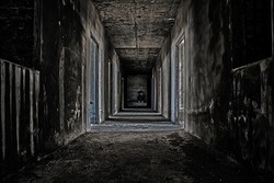 some people sitting in the room at end of scary hallway walkway in abandoned building