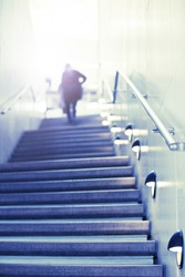 Some person walks up concrete stairs to toward the light at the top. Concept of success stairs.