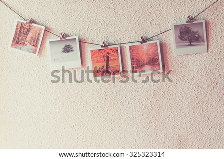Some photos hanging on a rope, white wall background
