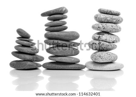 some piles of balanced stones on a white background