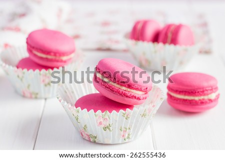 Some pink raspberry macaroons with floral paper cup on white shabby chic wooden background. Pastel colored composition with selective focus