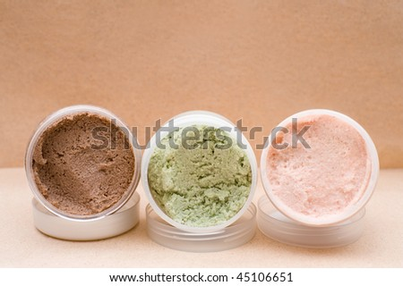 some plastic jars with coloured saline body scrub