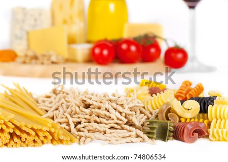Some popular kinds of the Italian pasta in the foreground and some kinds of the cheese, two glasses of wine, olive oil and tomatoes on a background. A shot horizontal, focus in the foreground.