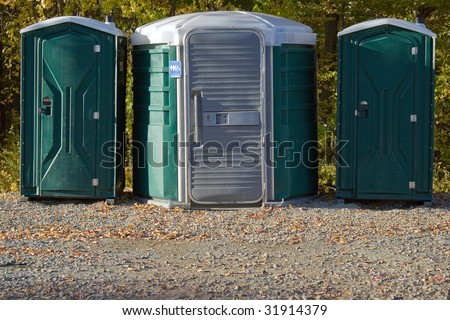 Some portable toilets located on the wooded hiking trail.