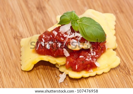 Some Raviolis with tomato sauce and Parmesan Cheese decorates with fresh basil on wooden background