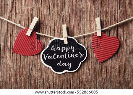 some red hearts hung with clothespins in a clothes line and a signboard in the shape of a thought-bubble with the text happy valentines day, against a rustic wooden background #552866005