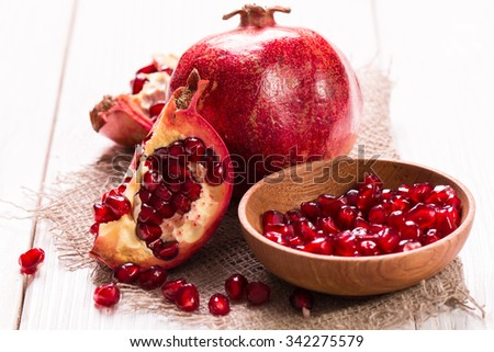 Some red juicy pomegranate, whole and broken, on  rustic wooden table.healthy food. #342275579