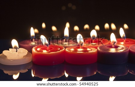 some red, white and purple candles glowing against a black background