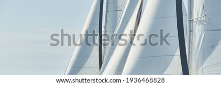 Some sails of white color, sailboats compete in a sailing regatta at sunset, sailing race