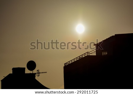 Some Silhouetted Antennas on the top of a Roof