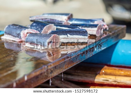 Some slices of fresh fish above a wooden table inside a fishermen boat. Traditional healthy food tempting our eyes with it freshness. A delicious freshly caught swordfish #1527598172