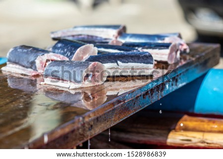 Some slices of fresh fish above a wooden table inside a fishermen boat. Traditional healthy food tempting our eyes with it freshness. A delicious freshly caught swordfish #1528986839