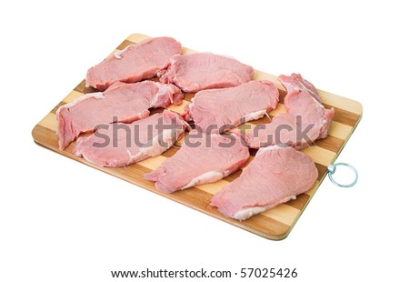 Some slices of tenderloin for cooking steaks lays on bamboo cutting hardboard. Isolated on a white background.