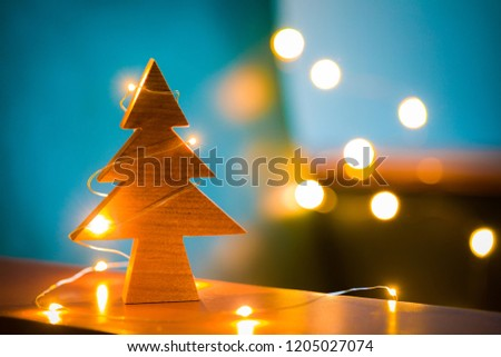 Some small lights are wrapped around a handmade cherry wood Christmas tree. Festive atmosphere indoor night view. Christmas atmosphere.