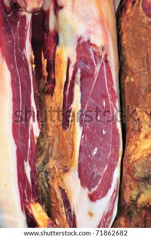 some spanish serrano hams hanging on a bar