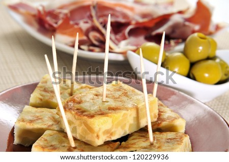 some spanish tapas, such as tortilla de patatas, serrano ham and olives