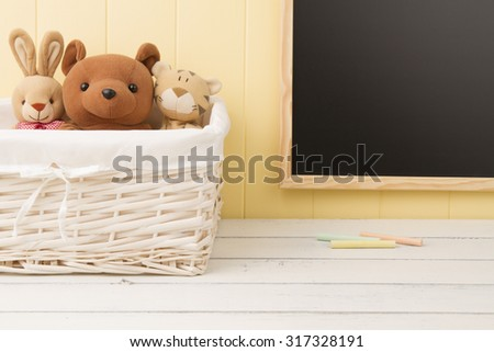 Some stuffed animal toys in a basket. A chalkboard in the background. Back to school.