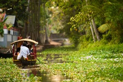 Some tourists are on a canoe sailing on the lush and green backwaters in Alleppey during the sunset, Kerala, India. Alleppey is one of the famous backwater tour destinations in Kerala.