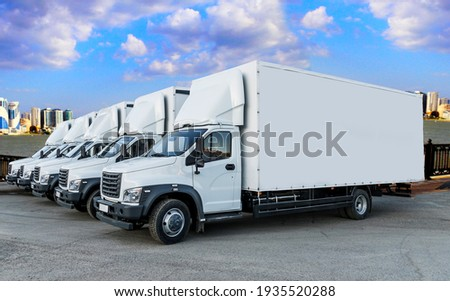 Some trucks are parked in a parking lot next to a logistics warehouse by the river. Several trucks are lined up in the parking lot. Logistic transport
