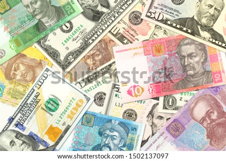 some ukrainian hryvnia banknotes and american dollar banknotes mixed indicating bilateral economic relations #1502137097