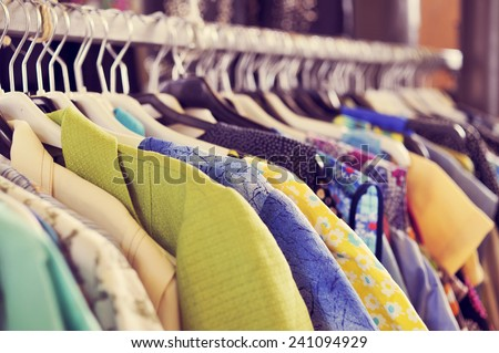 some used clothes hanging on a rack in a flea market #241094929