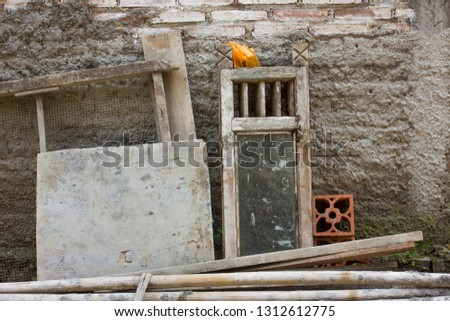 Some used wood, used bamboo and a used window leaning against an unfinished wall