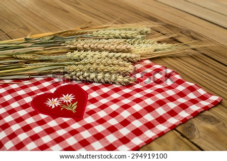 Some wheat, rye, barley ripe cereal ears on a background of red and white checkered tablecloth with a red heart and two embroidered white Edelweiss on rustic wooden table surface