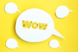 Some white paper speech bubbles concept with inscription wow. Cartoon speech with clipping path on bright yellow background with contrasting shadow