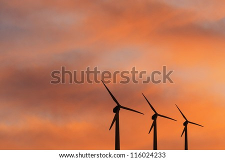 Some wind turbines silhouette in the sunset sky