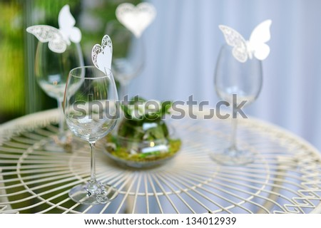 Some wine glasses decorated with paper butterflies