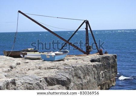some wooden fishing boats on cliff edge with crane