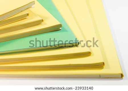 some yellow books and one green isolated on white background