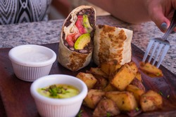 somebody has put their fork into a tasty vegan plate. The dish is a bean burrito served with sauteed potatoes and a green salad