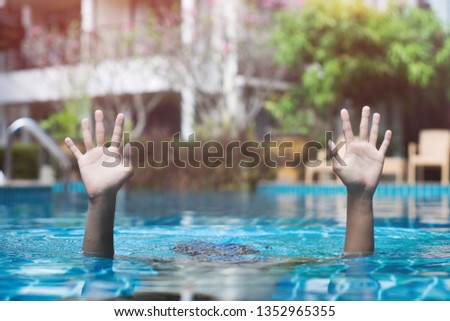 Somebody help.Man get drowning in the swimming pool and show his hand for asking some help.Crisis life concept.