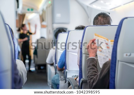 somebody is reading the menu on the seat in the plane, and ready to order to air hostess. ストックフォト ©