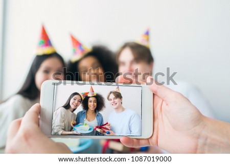 Somebody is taking picture on the phone. There are a girl that has birthday and her friends that are gathered together. They are posing and smiling ro camera. Stock foto ©