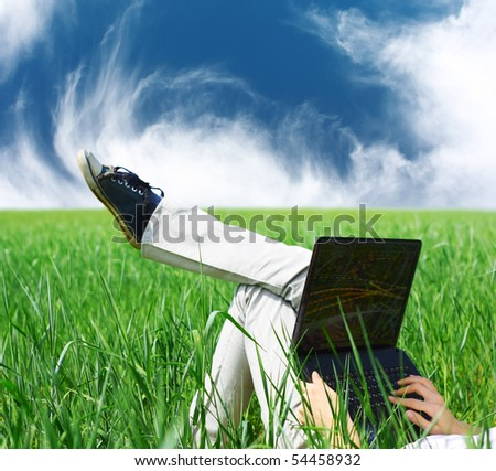 Somebody lying in green grass with laptop