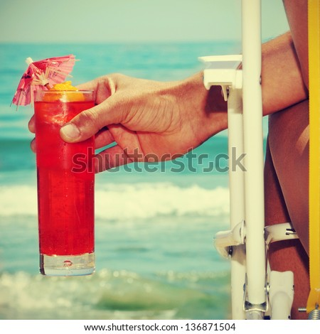 someone chilling out with a cocktail on the beach, with a retro effect